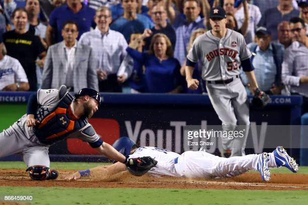 Logan Forsythe of the Los Angeles Dodgers scores a run on a RBI single hit by Enrique Hernandez to tie the game 55 during the tenth inning against...