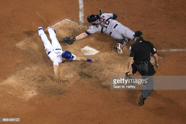Logan Forsythe of the Los Angeles Dodgers scores a run on a RBI single hit by Enrique Hernandez to tie the game 55 during the tenth inning as Brian...