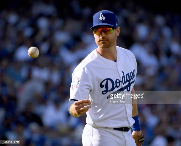 Logan Forsythe of the Los Angeles Dodgers tosses the ball back afterhis catch for an out of Brandon Crawford of the San Francisco Giants during the...