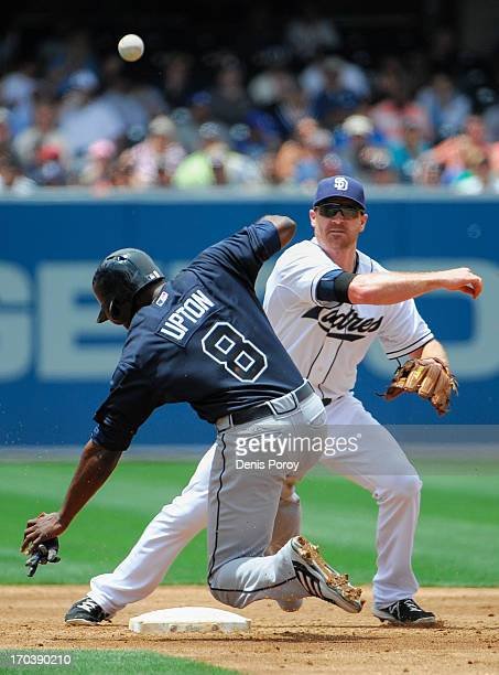 Logan Forsythe of the San Diego Padres throws over Justin Upton of the Atlanta Braves as he turns a double play during the third inning of a baseball...