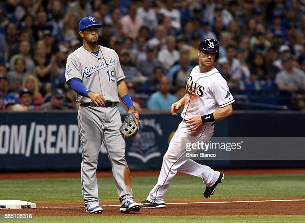 Logan Forsythe of the Tampa Bay Rays advances to third base ahead of third baseman Cheslor Cuthbert of the Kansas City Royals off of a throwing error...