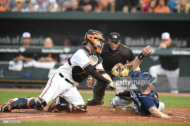 Logan Forsythe of the Tampa Bay Rays beats the tag by Caleb Joseph of the Baltimore Orioles on a fly ball sacrifice hit by Tim Beckham in the second...