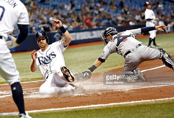 Logan Forsythe of the Tampa Bay Rays slides home ahead of catcher Kurt Suzuki of the Minnesota Twins to score off of an RBI single by Nick Franklin...