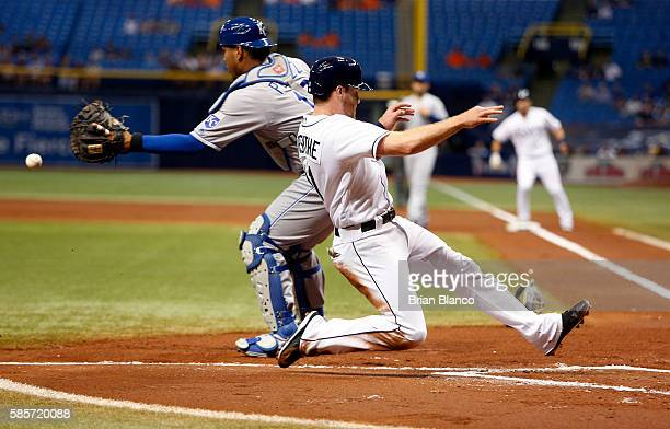 Logan Forsythe of the Tampa Bay Rays slides safely home ahead of catcher Paulo Orlando of the Kansas City Royals to score off of a sacrifice fly by...