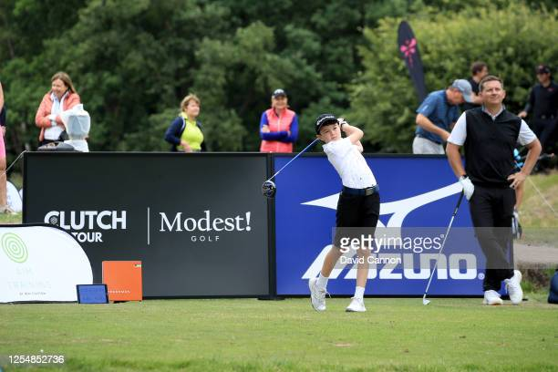 Logan Hodgson of England a junior member of Sunningdale Heath hits a shot off the first tee watched his club professional Tom Reid during the pro-am...