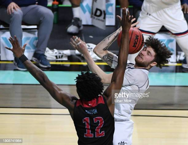 Logan Johnson of the Saint Mary's Gaels is fouled by Jalin Anderson of the Loyola Marymount Lions during the West Coast Conference basketball...