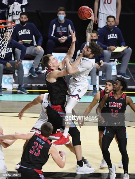 Logan Johnson of the Saint Mary's Gaels is fouled by Mattias Markusson of the Loyola Marymount Lions on a dunk attempt during the West Coast...