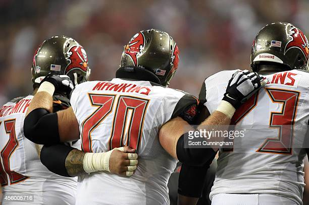 Logan Mankins of the Tampa Bay Buccaneers is helped off the field by Evan Deitrich-Smith and Anthony Collins after being injured against the Atlanta...