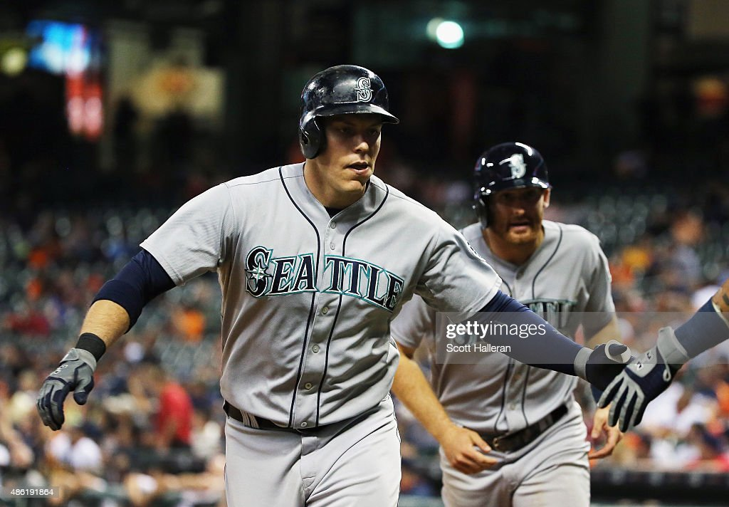 Logan Morrison #20 and Brad Miller #5 of the Seattle Mariners come in to score after Morrison hit a two-run home run in the eighth inning of their game against the Houston Astros at Minute Maid Park on September 1, 2015 in Houston, Texas.