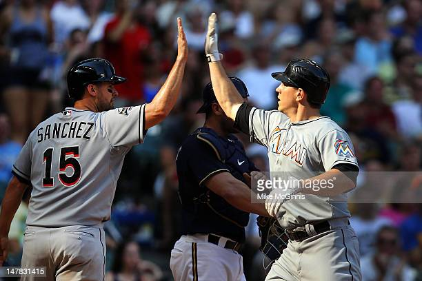 Logan Morrison of the Miami Marlins high fives Gaby Sanchez after hitting a 3 run homer in the top of the 7th inning tying up the game 55 against the...