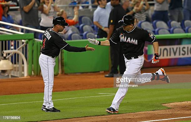 Logan Morrison of the Miami Marlins high fives third base coach Joe Espada after hitting a two run home run in the second inning during a game...