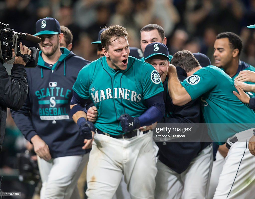 Logan Morrison #20 of the Seattle Mariners (C) celebrates hitting a walk-off homerun in the eleventh inning of a game against the Oakland Athletics at Safeco Field on May 8, 2015 in Seattle, Washington. The Mariners won the game 4-3