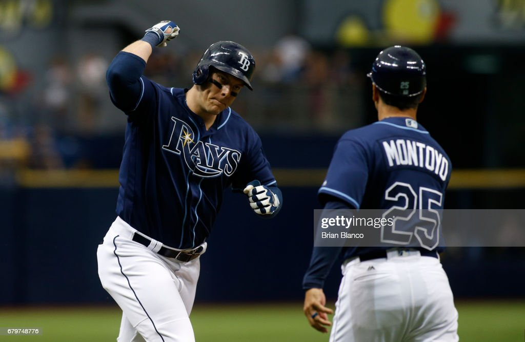 Logan Morrison #7 of the Tampa Bay Rays celebrates with third base coach Charlie Montoyo #25 after hitting a two-run home run during the third inning of a game against the Toronto Blue Jays on May 6, 2017 at Tropicana Field in St. Petersburg, Florida.