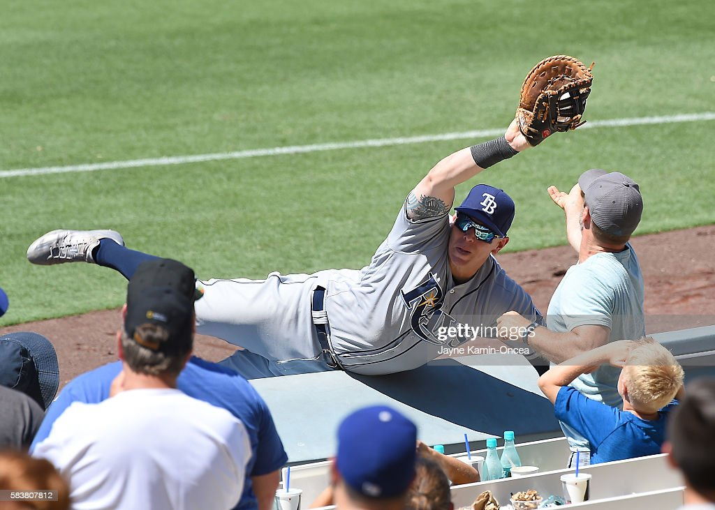 Logan Morrison #7 of the Tampa Bay Rays falls over the rail after catching a pop foul by Howie Kendrick #47 of the Los Angeles Dodgers in the seventh inning of the game at Dodger Stadium on July 27, 2016 in Los Angeles, California.