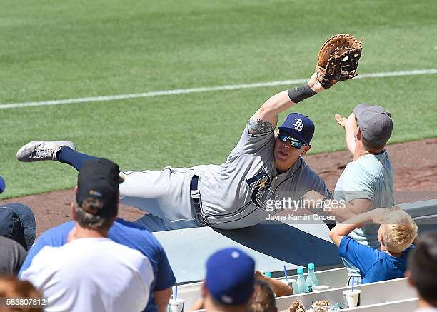 Logan Morrison of the Tampa Bay Rays falls over the rail after catching a pop foul by Howie Kendrick of the Los Angeles Dodgers in the seventh inning...