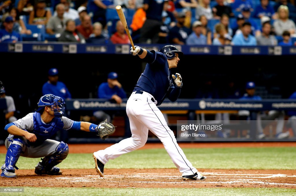 Logan Morrison #7 of the Tampa Bay Rays follows through as he hits an RBI double in front of catcher Luke Maile #22 of the Toronto Blue Jays to score Evan Longoria during the sixth inning of a game on May 6, 2017 at Tropicana Field in St. Petersburg, Florida.