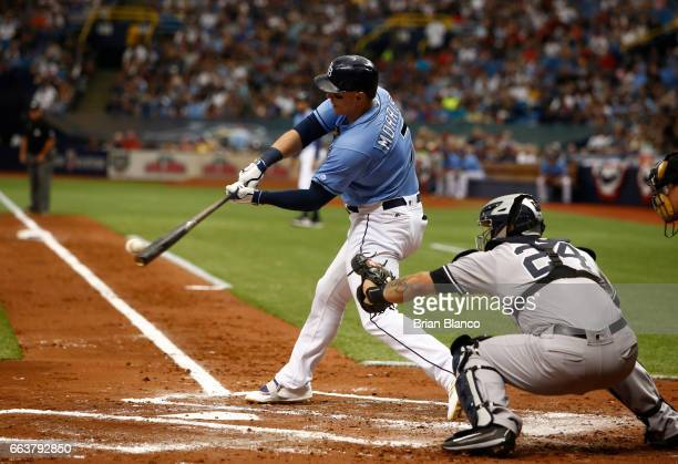 Logan Morrison of the Tampa Bay Rays hits a tworun single in front of catcher Gary Sanchez of the New York Yankees during the first inning of a game...