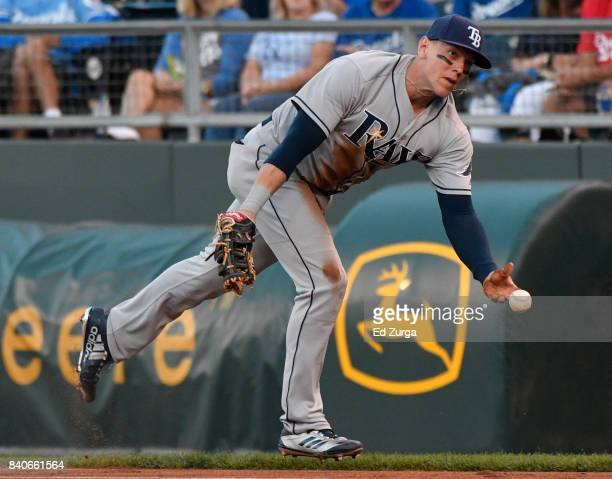 Logan Morrison of the Tampa Bay Rays tosses the ball to Alex Cobb as he tries to get the force out at first on Lorenzo Cain of the Kansas City Royals...
