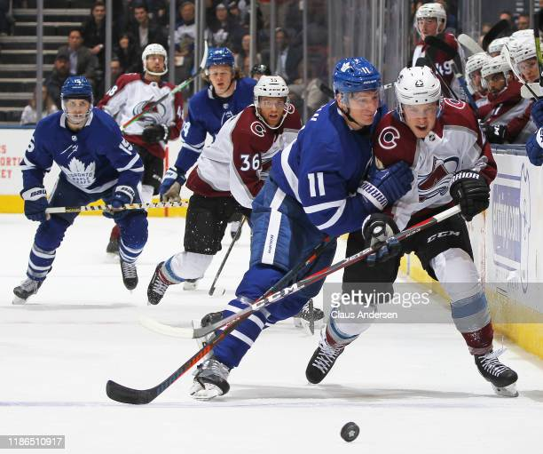 Logan O'Connor of the Colorado Avalanche takes a hit from Zach Hyman of the Toronto Maple Leafs during an NHL game at Scotiabank Arena on December 4...