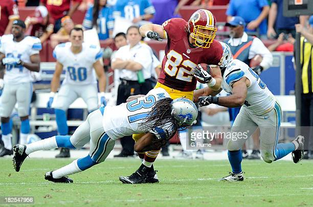 Logan Paulsen of the Washington Redskins is tackled by Rashean Mathis and DeAndre Levy of the Detroit Lions at FedExField on September 22, 2013 in...
