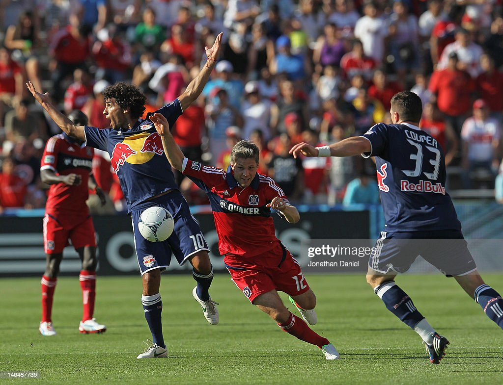 Logan Pause #12 of the Chicago Fire pushes the ball between a complaining Mehdi Ballouchy #10 (L) and Kenny Cooper #33 of the New York Red Bulls during an MLS match at Toyota Park on June 17, 2012 in Bridgeview, Illinois. The Fire defeated the Red Bulls 3-1.