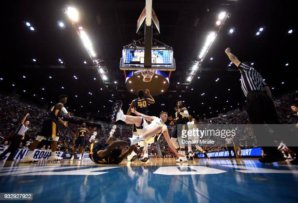 Logan Routt of the West Virginia Mountaineers collides with Shaq Buchanan of the Murray State Racers during the first round of the 2018 NCAA Men's...