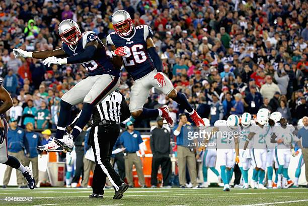 Logan Ryan of the New England Patriots reacts with Michael Williams after intercepting a pass during the second quarter against the Miami Dolphins at...