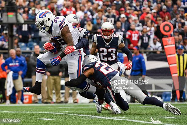 Logan Ryan of the New England Patriots tackles Mike Gillislee of the Buffalo Bills in the first quarter at Gillette Stadium on October 2, 2016 in...