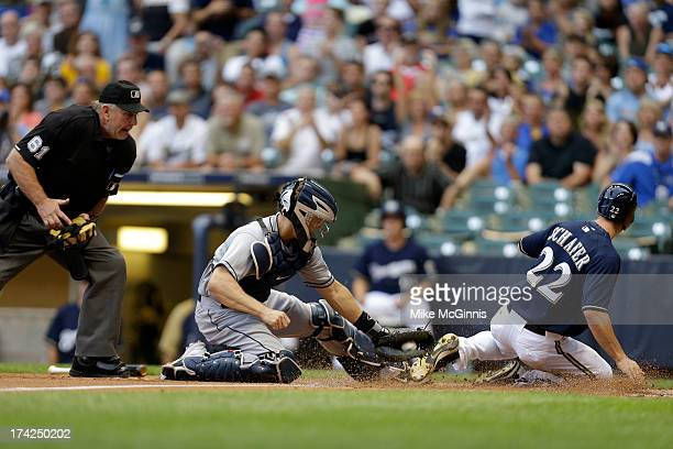 Logan Schafer of the Milwaukee Brewers avoids the tag from Nick Hundley of the San Diego Padres while crossing home plate on a double hit by Jean...