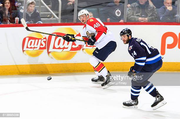 Logan Shaw of the Florida Panthers and Anthony Peluso of the Winnipeg Jets watch the puck fly down the ice during second period action at the MTS...