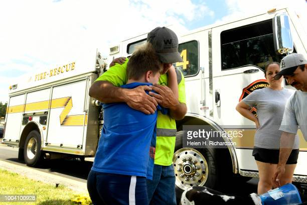 Logan Spiegel hugs his father Tom left at the scene of a deadly apartment complex fire at the Westbury Apartments on July 22 in Westminster Colorado...
