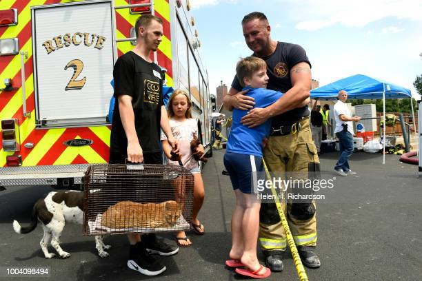 Logan Spiegel hugs Westminster firefighter Nate Olson right for rescuing his cat out of his apartment at the scene of a deadly apartment complex fire...