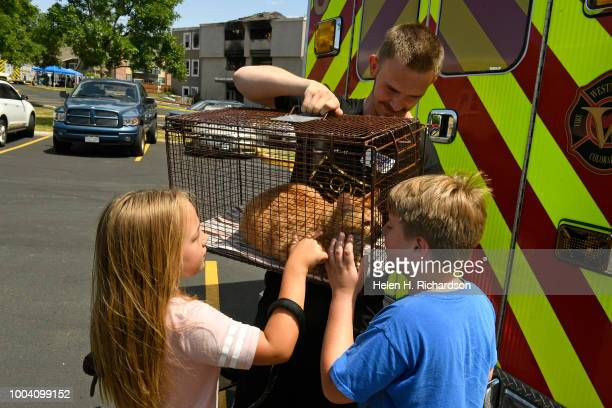 Logan Spiegel left and his niece Kiara Bering left pet their recently rescued cat as family friend Skyler McQuigg holds up the cage near the scene of...