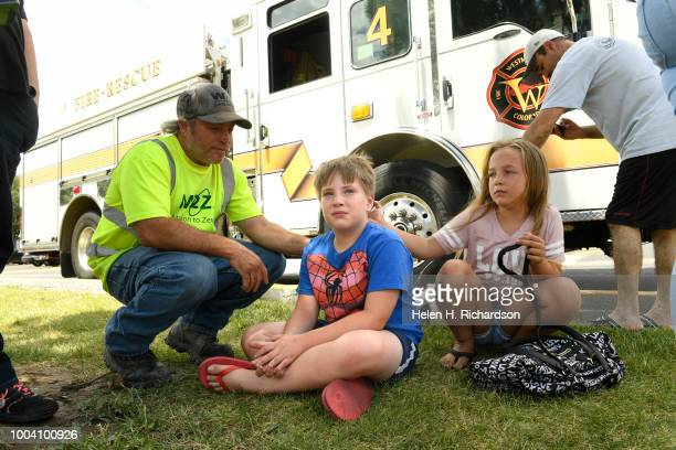 Logan Spiegel middle gets comforted by his father Tom left and family member Kiara Bering as he watches firefighters work at the scene of a deadly...