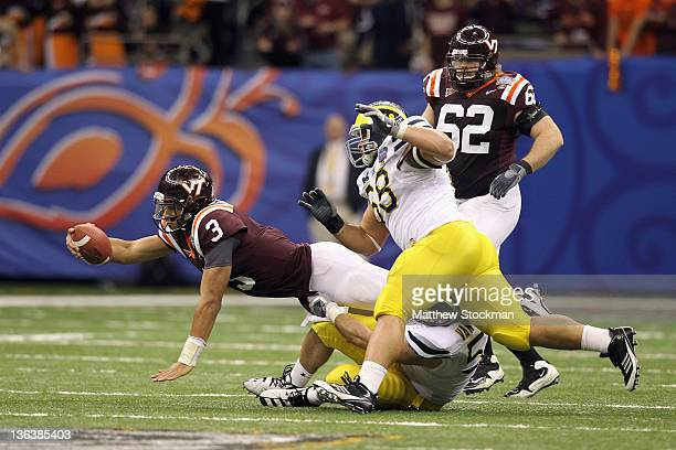 Logan Thomas of the Virginia Tech Hokies attempts to reach for extra yardage as he is tackeled by Ryan Van Bergen and Mike Martin of the Michigan...