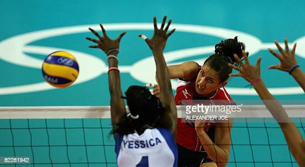 Logan Tom of the US slams a shot onto Yessica Paz Hidalgo of Venezuela during a women's preliminary volleyball match of the 2008 Beijing Olympic...