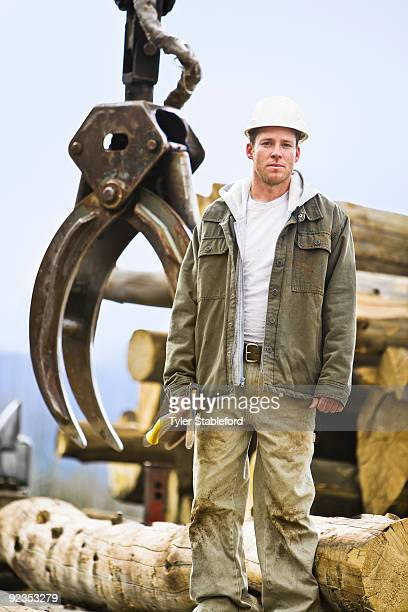 Logger standing in front of mechanical claw.