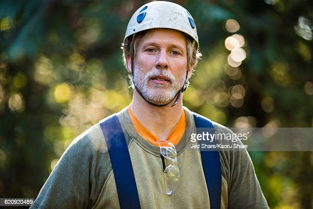 Logger wearing hat and suspenders outdoors
