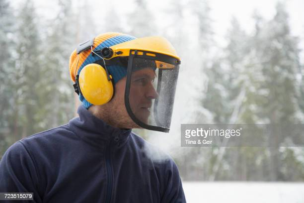 Logger wearing safety visor in forest, Tammela, Forssa, Finland
