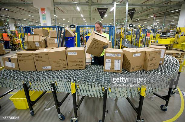 Logistic center of Amazon Germany GmbH in Koblenz A man grasps packets on a treatmill