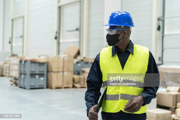 logistic worker with face protection at work - longshoremen stock pictures, royalty-free photos & images