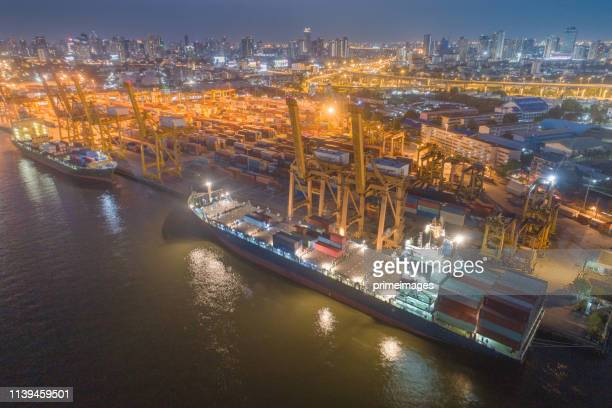 コンテナ貨物船と貨物機の物流と輸送は、日の出の造船所でクレーン橋を使用して、ロジスティック輸入の輸出と輸送業界の背景 - indonesia logistics ストックフォトと画像