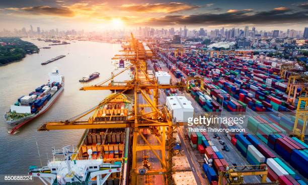 logistics and transportation of container cargo ship and cargo plane with working crane bridge in shipyard - economy stock pictures, royalty-free photos & images