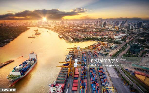 Logistics and transportation of Container Cargo ship and Cargo plane with working crane bridge in shipyard