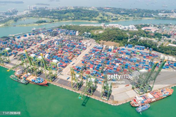 造船所におけるクレーン橋を使用したコンテナ貨物船・貨物の物流・輸送業務、物流輸出入業の背景 - indonesia logistics ストックフォトと画像