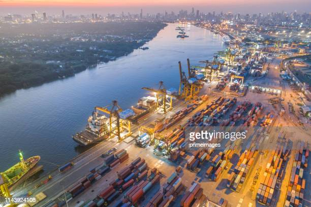 logistics and transportation of container cargo ship and cargo with working crane bridge in shipyard at sunrise, logistic import export and transport industry background - japan economy stock pictures, royalty-free photos & images