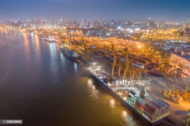 日の出時の造船所での作業クレーン橋を持つコンテナ貨物船と貨物の物流と輸送、物流輸入輸出・輸送業界の背景 - indonesia logistics ストックフォトと画像