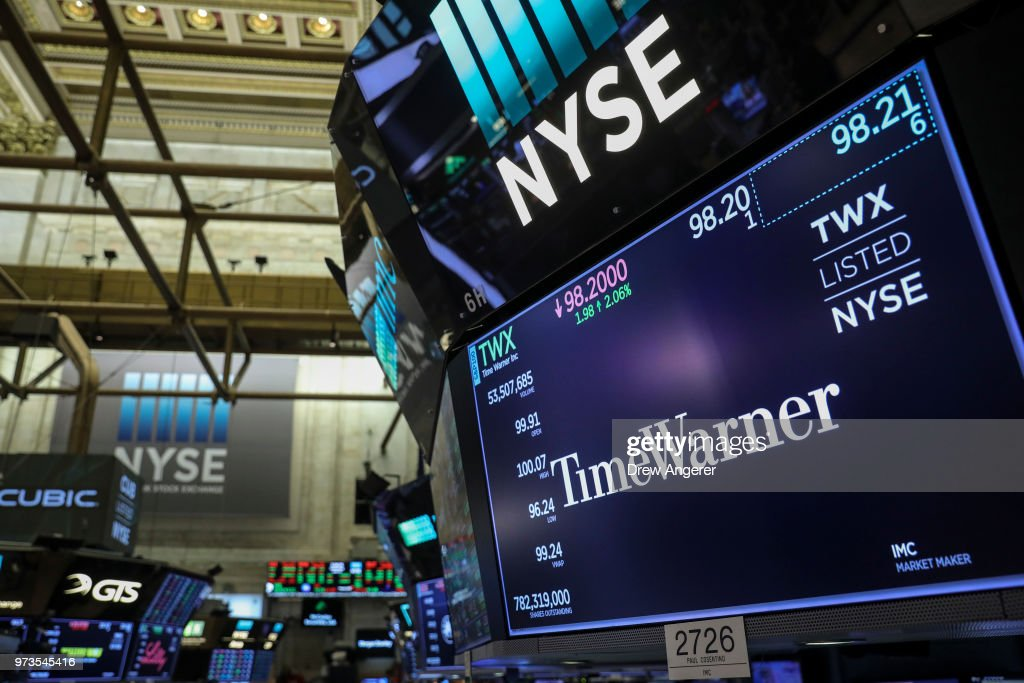 A logo and trading information for Time Warner is displayed on a monitor on the floor of the New York Stock Exchange (NYSE) June 13, 2018 in New York City. Following news today that the Federal Reserve raised interest rates a quarter percentage point, the Dow Jones Industrial Average was down 119 points at the close.