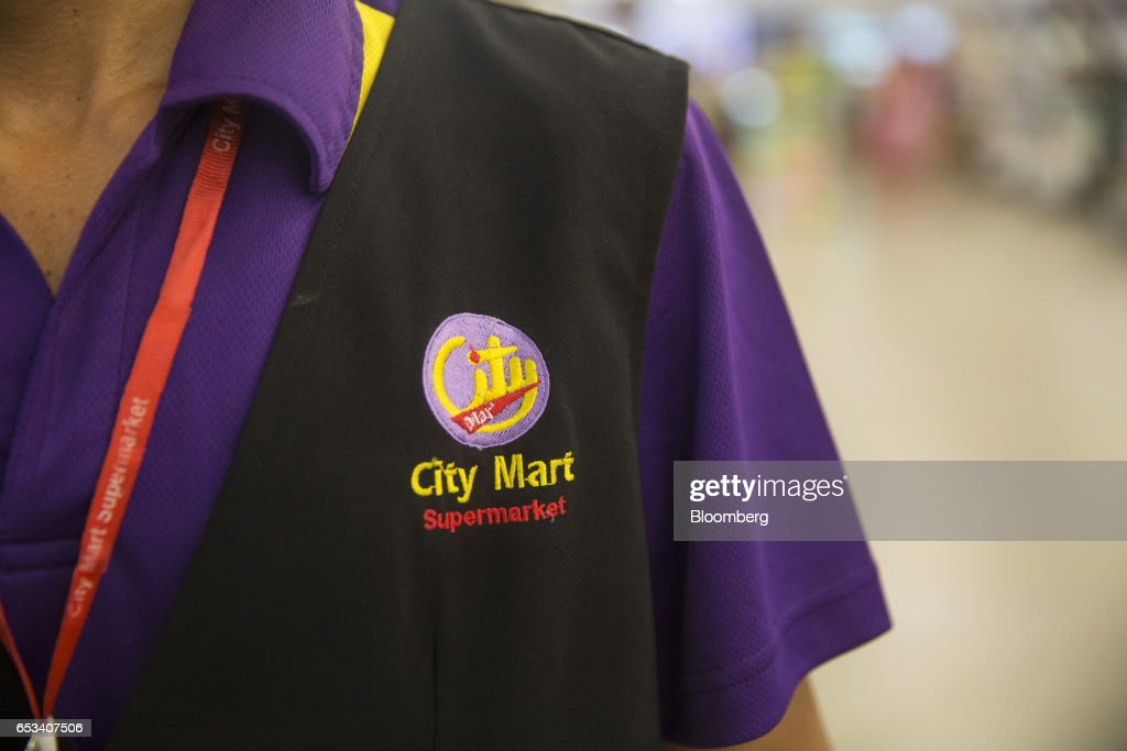 A logo for City Mart Supermarket, operated by City Mart Holdings Co., is displayed on an employee's uniform at a store in Yangon, Myanmar, on Saturday, March 11, 2017. City Mart has 20 years of market knowledge to help it compete against international players, said Win Win Tint, managing director of City Mart in a Bloomberg interview on March 9. Photographer: Brent Lewin/Bloomberg via Getty Images