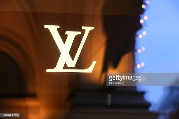 A 'VL' logo for Louis Vuitton products a unit of LVMH Moet Hennessy Vuitton SE sits on the window of the GUM luxury department store on Red Square in...